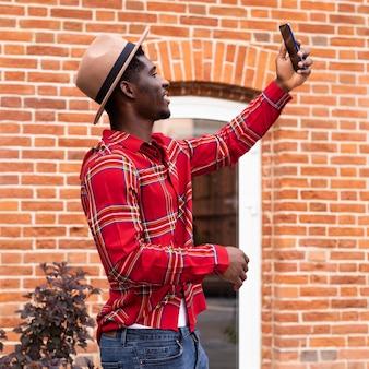 Vista lateral do turista tirando uma selfie