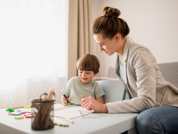 Vista lateral do tutor ensinando criança em casa