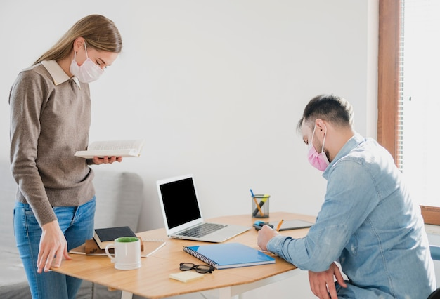 Vista lateral do tutor feminino e estudante do sexo masculino em casa