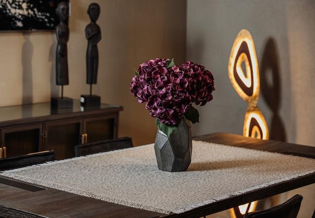 Vista lateral do vaso preto moderno com flores roxas numa toalha de mesa em cima da mesa