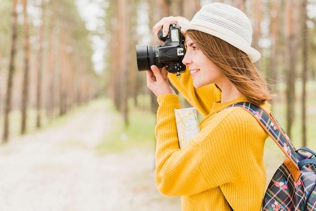 Vista lateral do viajante tirando uma foto