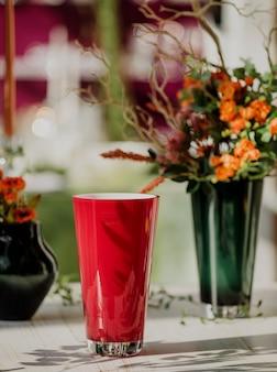 Vista lateral do vidro de cor vermelha para água ou suco em cima da mesa com flores em um vaso na parede