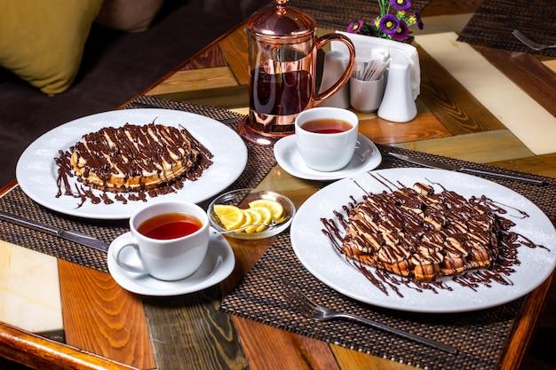 Vista lateral do waffle com bananas cobertas com chocolate no prato branco, servido com chá na mesa