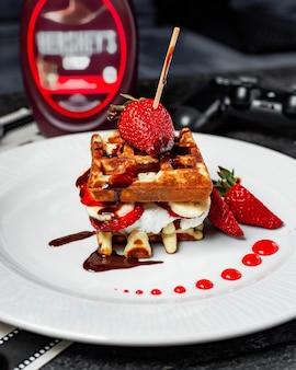Vista lateral do waffle com sorvete de morangos e bananas cobertas com calda de chocolate no prato branco