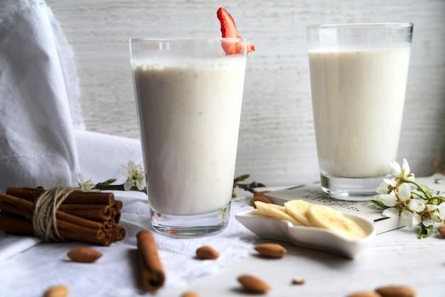 Vista lateral, dois copos de leite com canela e banana fatiada e strawberrie