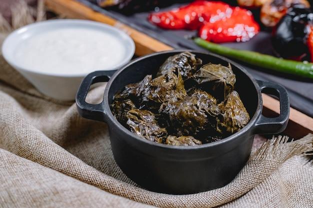 Vista lateral dolma folhas de uva recheada com carne moída cebola verdes e iogurte em cima da mesa
