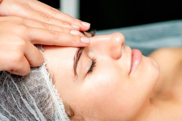 Vista lateral dos dedos de uma terapeuta fazendo uma massagem anti-envelhecimento das rugas da testa em uma jovem mulher caucasiana em um salão de beleza do spa