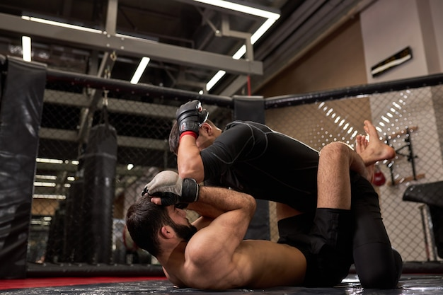 Vista lateral dos lutadores de boxeadores de mma lutando sem regras no ringue da gaiola da academia. lutadores de mma em ringue se preparando para o campeonato. lutas de boxe sem regras