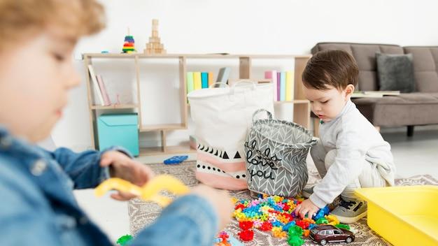 Vista lateral dos meninos em casa brincando com brinquedos