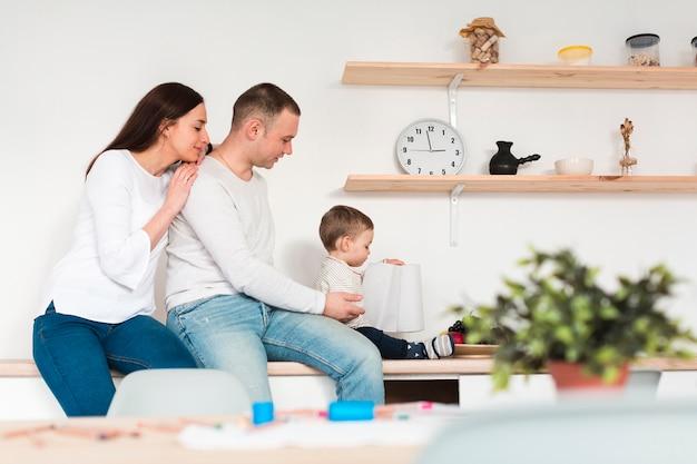Vista lateral dos pais com o filho na cozinha