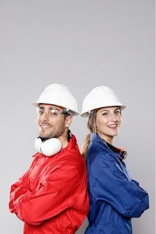 Vista lateral dos trabalhadores da construção civil posando