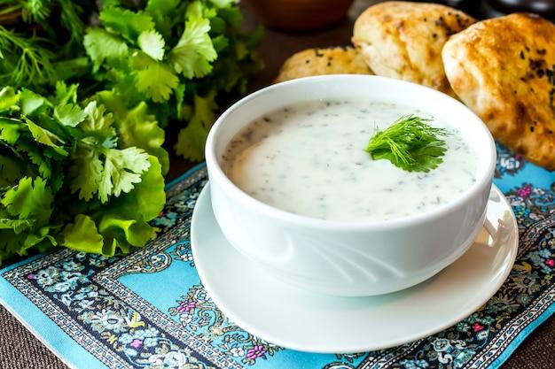 Vista lateral dovga sopa de iogurte com salsa e pão