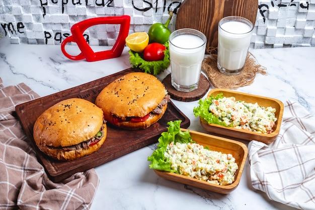 Vista lateral duas porções de carne doner no pão com duas porções de salada capital e dois copos de iogurte