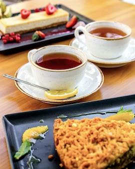 Vista lateral duas xícaras de chá com uma fatia de limão e sobremesas em cima da mesa