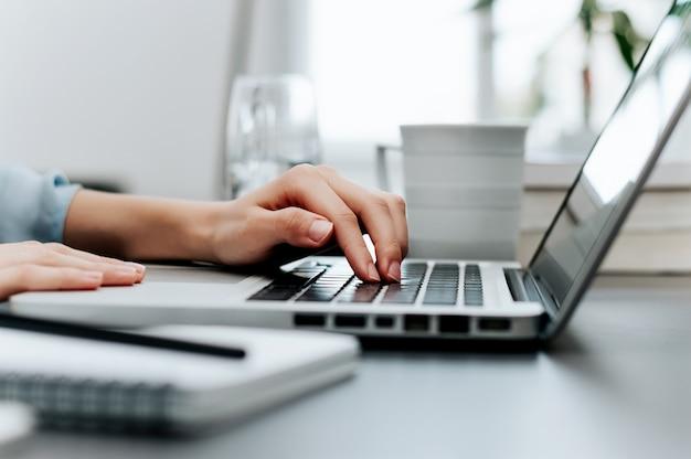Vista lateral e close-up das mãos da mulher, digitando no teclado do laptop.