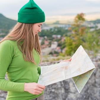 Vista lateral elegante viajante com gorro verificar mapa