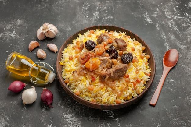Vista lateral em close-up arroz pilaf cebola alho garrafa de colher de óleo na mesa