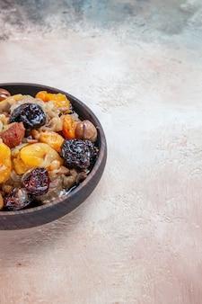 Vista lateral em close-up arroz pilaf frutas secas castanhas na mesa