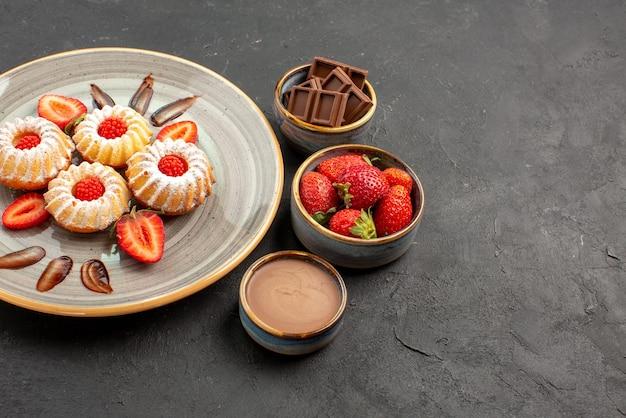 Vista lateral em close-up cookies de chocolate e morango tigelas de morango com chocolate e creme de chocolate ao lado do prato de biscoitos com morangos na mesa