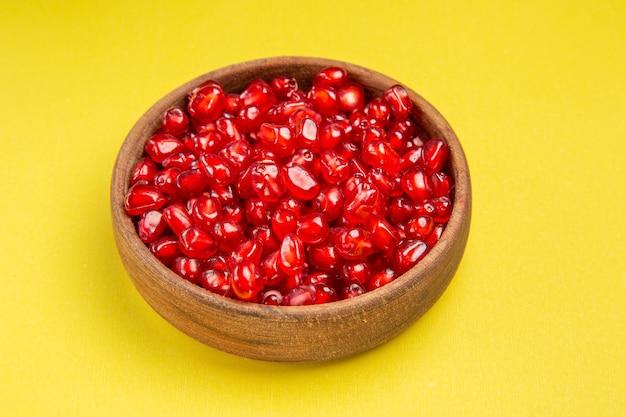 Vista lateral em close-up da romã as sementes apetitosas de romã na tigela marrom