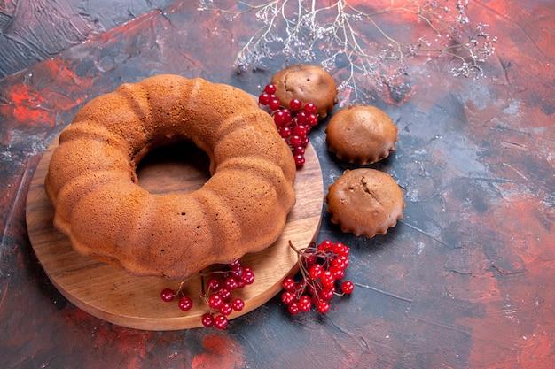 Vista lateral em close-up da tábua de cortar bolo com bolo e groselha ao lado dos cupcakes