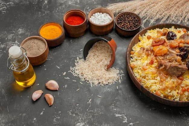 Vista lateral em close-up de arroz pilaf com tigelas de carne com especiarias e arroz com alho e garrafa de óleo