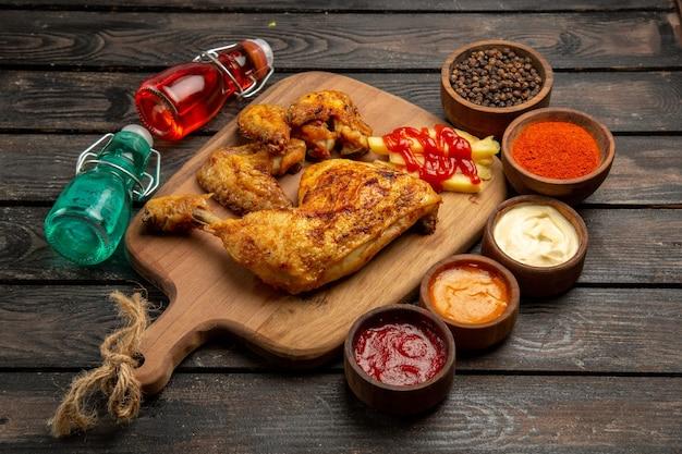 Vista lateral em close-up de frango com coxa e asas de frango com batata frita e ketchup na tábua de cortar ao lado dos molhos de pimenta preta, especiarias e garrafas vermelhas e azuis