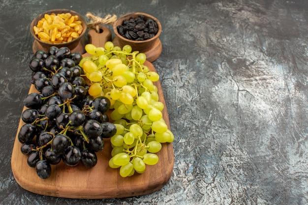 Vista lateral em close-up de frutas, cachos de uvas verdes e pretas no tabuleiro de tigelas de frutas secas