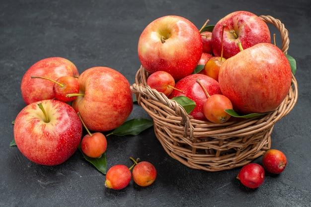 Vista lateral em close-up de frutas, maçãs e cerejas amarelo-avermelhadas na cesta