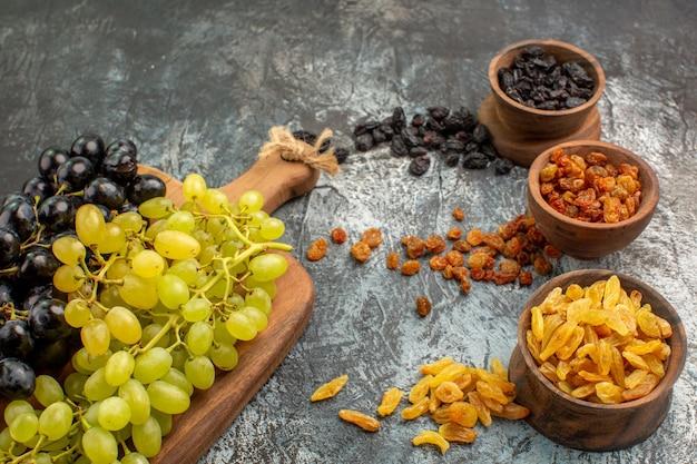 Vista lateral em close-up de frutas secas, frutas secas em tigelas marrons e uvas na placa de madeira
