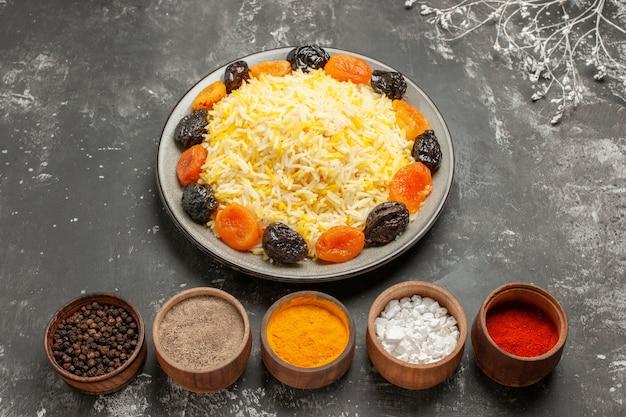 Vista lateral em close-up de tigelas de arroz com prato de especiarias e arroz com frutas secas