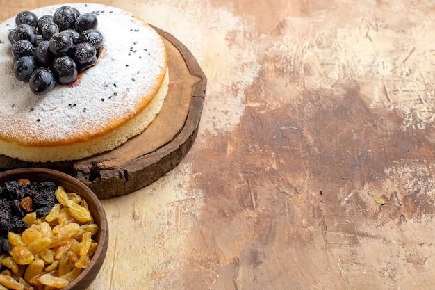 Vista lateral em close-up de uma tigela de bolo de passas um bolo apetitoso com uvas pretas no tabuleiro
