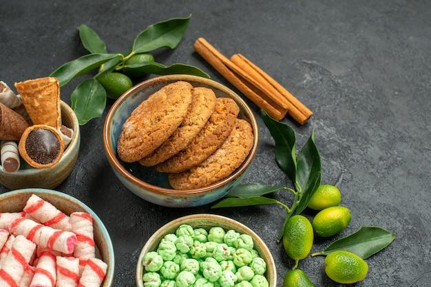 Vista lateral em close-up doces em bastões de canela doces coloridos frutas cítricas waffles biscoitos