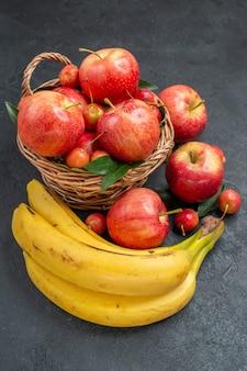 Vista lateral em close-up frutas bananas cesta de madeira com maçãs e cerejas