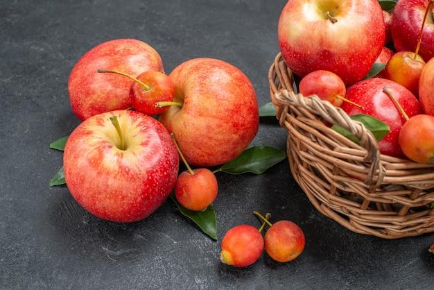 Vista lateral em close-up, frutas, cerejas e maçãs vermelho-amarelas na cesta