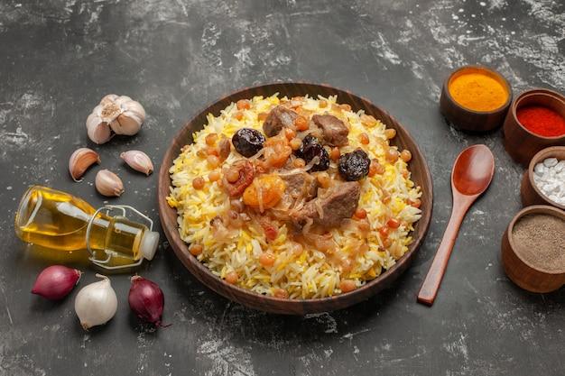 Vista lateral em close-up óleo de arroz cebola alho um pilaf apetitoso com colher de especiarias de frutas secas