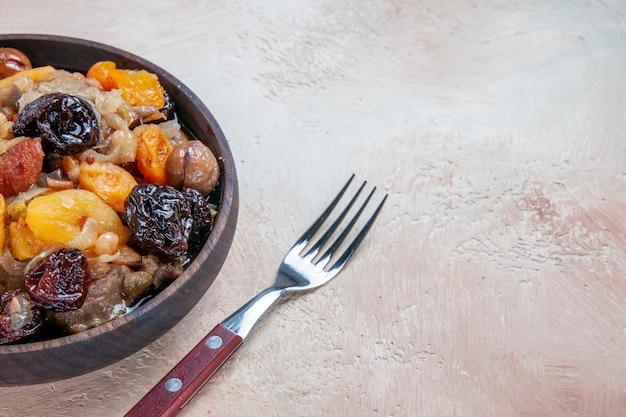Vista lateral em close-up pilaf arroz castanhas frutas secas no garfo tigela