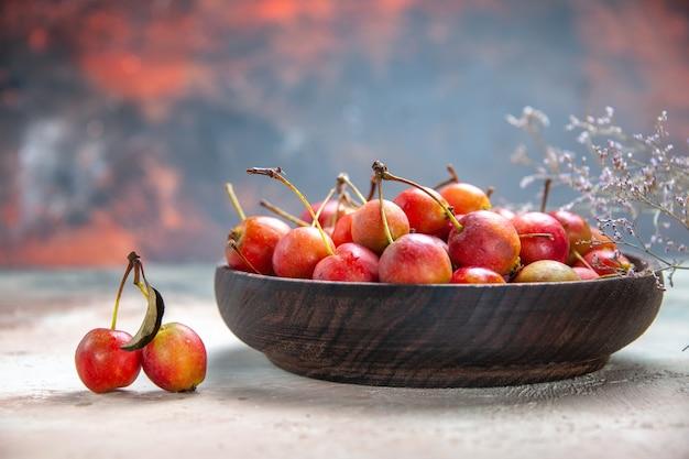 Vista lateral em close-up tigela de madeira das cerejas das cerejas abranches