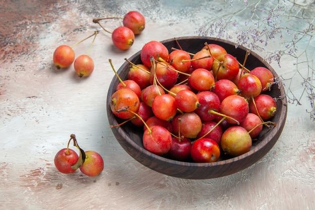 Vista lateral em close-up tigela marrom das cerejas dos ramos apetitosos das cerejas