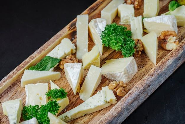 Vista lateral em fatias de queijo roquefort com ervas e nozes em uma placa de madeira