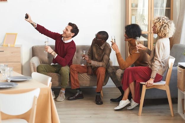 Vista lateral em um grupo multiétnico de adultos modernos tirando uma selfie com taças de champanhe dentro de casa enquanto desfruta de um jantar com amigos.