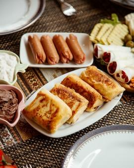 Vista lateral enrolada panquecas com salsichas em cima da mesa