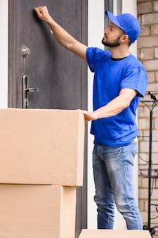 Vista lateral entregador batendo na porta