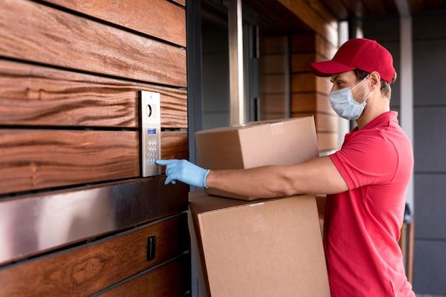 Vista lateral entregador tocando na porta