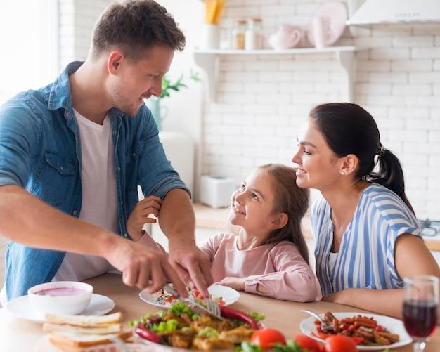 Vista lateral família comendo juntos