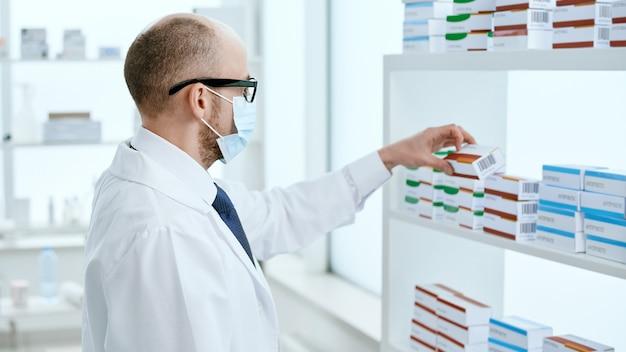 Vista lateral. farmacêutico em uma máscara protetora leva uma caixa com um novo medicamento.