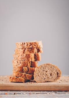 Vista lateral fatiada de pão na tábua na mesa de madeira e superfície cinza
