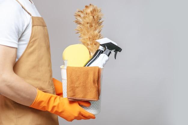 Vista lateral, feche a mão de um jovem de avental e luvas de borracha segurando uma cesta de equipamentos de limpeza, o espanador, o borrifador, a esponja e um pano para limpar na cesta