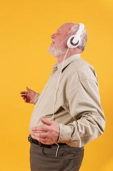 Vista lateral feliz ouvindo música sênior