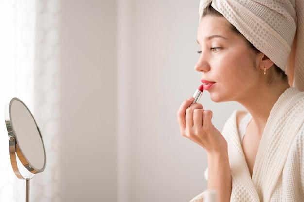 Vista lateral feminina aplicar lábios maquiagem